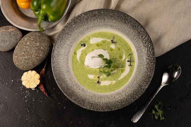 Kremowa zupa szpinakowa z jajkiem w koszulce, doprawiona śmietaną, sosem aioli i mikrogreenem z kiełków grochu