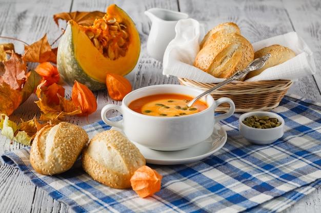Kremowa zupa z dyni piżmowa zwieńczona pestkami dyni i śmietaną na rustykalnym tle drewna z jesiennych liści