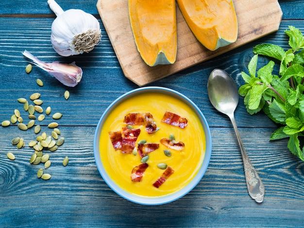 Kremowa zupa z dyni z boczkiem i nasionami na ciemnym niebieskim tle drewna, czosnku, mięty