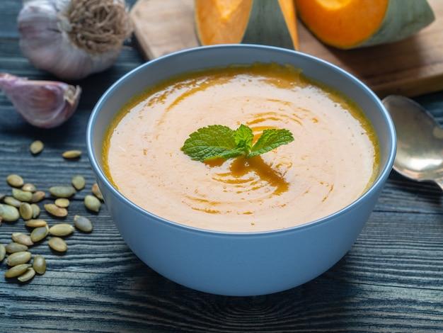 Kremowa zupa z dyni z miętą na ciemnym niebieskim tle drewniane, czosnek, plastry dyni.