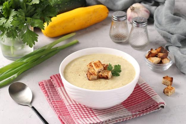 Kremowa zupa z kurczaka i cukinii podawana z grzankami z białego chleba w misce na szarym tle.