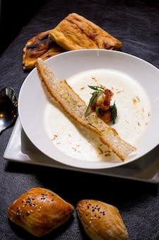 Kremowa zupa z owoców morza krewetek krakersy bułki szafran widok z boku