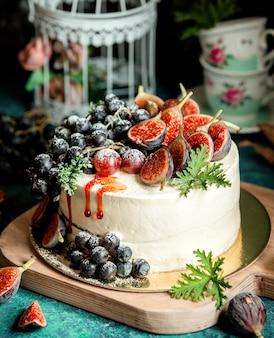 Kremowe białe ciasto ozdobione połówkami fig i winogronem