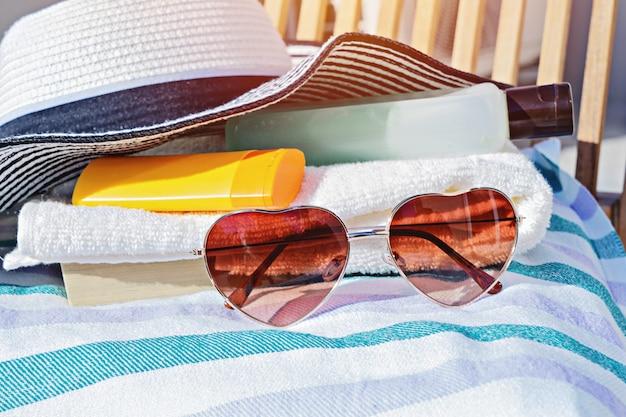 Kremowe butelki kosmetyczne, okulary przeciwsłoneczne i letni kapelusz na leżaku