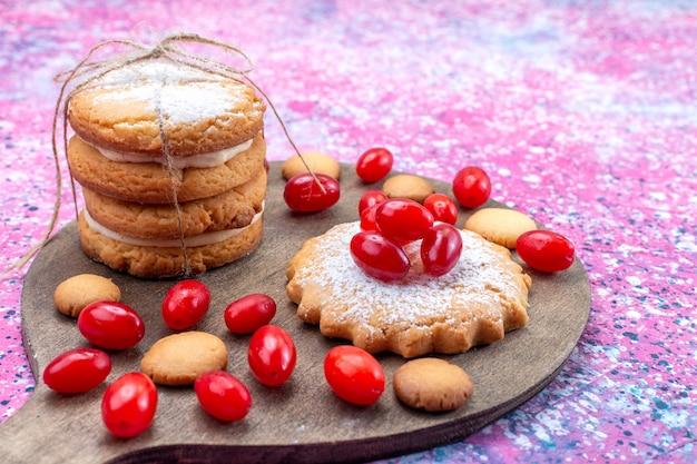 Kremowe ciasteczka kanapkowe z czerwonymi dereniami na jasnych, ciasteczkowych ciasteczkach biszkoptowo-kwaśnych jagodach