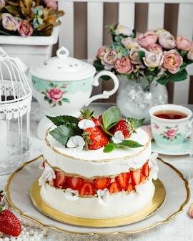 Kremowe ciasto truskawkowe zwieńczone świeżymi truskawkami i liśćmi