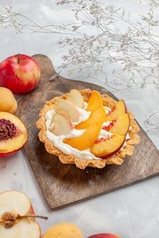 Kremowe ciasto z pokrojonymi owocami i białą śmietaną wraz ze świeżymi owocami na jasnym białym biurku, zapiekanka z kremem owocowym