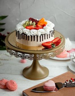 Kremowe ciasto z truskawkami na stole
