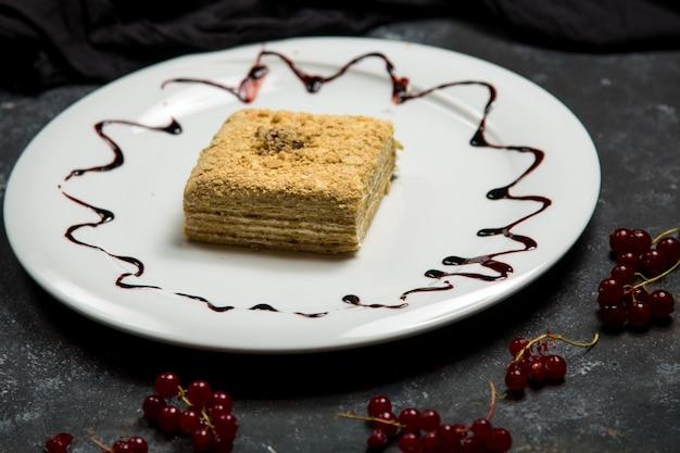 Kremowe ciasto zwieńczone orzechiem włoskim