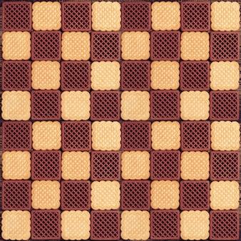 Kremowe i czekoladowe ciasteczka jako szachownica. może być używany jako tło