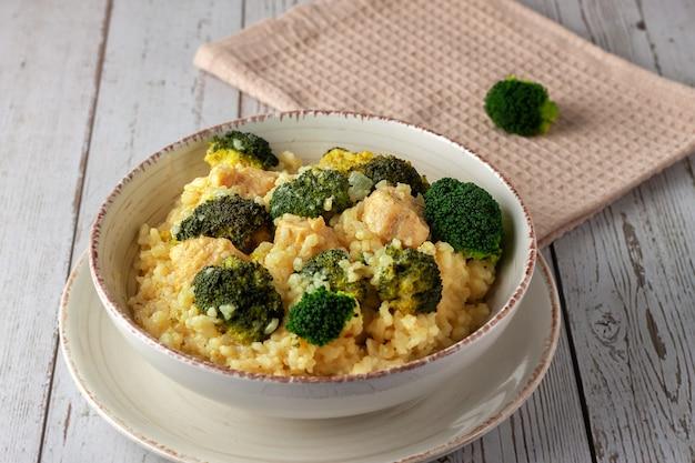 Kremowe risotto z kurczakiem i brokułami w talerzu na drewnianym tle