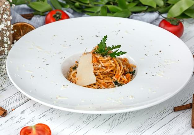Kremowe spaghetti marchewkowe z pomidorami, przyozdobione natką pietruszki i parmezanem