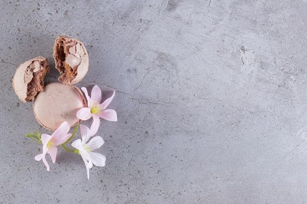 Kremowo-brązowe makaroniki z pastelowymi kwiatami na marmurowym stole.