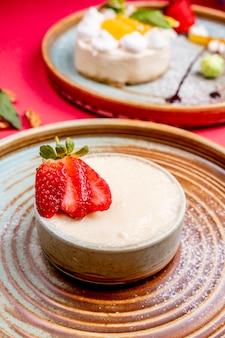 Kremowy deser zwieńczony krojoną truskawką