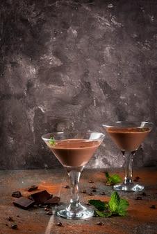 Kremowy kawowy koktajl, czekoladowy martini z mennicą na czerń kamienia stole, copyspace