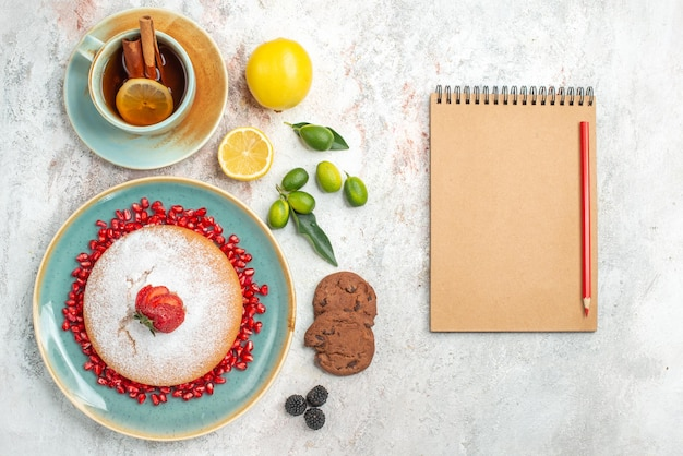Kremowy notatnik czerwony ołówek obok talerza z ciastem z truskawkami i granatem na stole ciasteczka cytrusowe