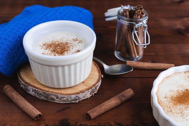 Kremowy pudding ryżowy i cynamon na drewnianej podstawie. koncepcja ciasta.