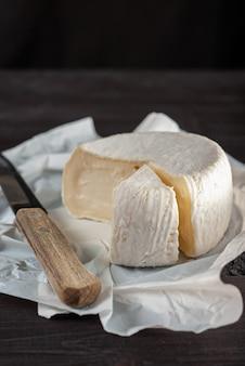 Kremowy ser camembert na naturalnym ciemnym drewnianym tle