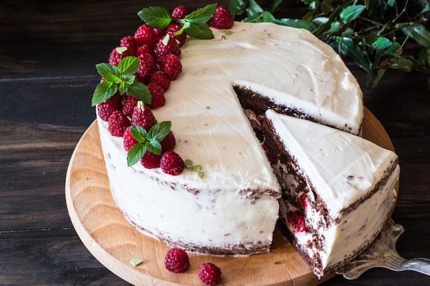Kremowy tort owocowy. malinowy tort z czekoladą. ciasto czekoladowe. wystrój mięty. sernik.