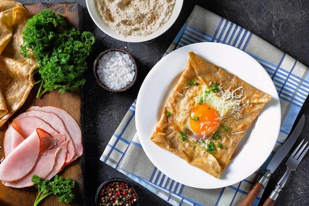 Krepa bretońska, pikantne galettes z kaszy gryczanej bretonne z jajkiem sadzonym, serem, szynką na białym talerzu na stole kuchennym ze składnikami na desce do krojenia, widok z góry, flatlay