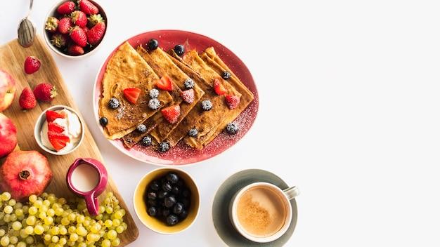 Krepa z zdrowym śniadaniem i kawą nad białym tłem