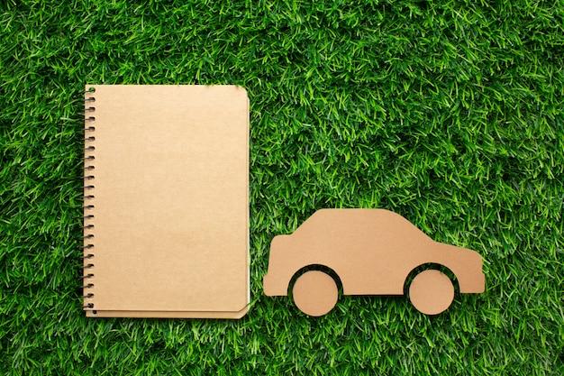 Kreskówka samochód i notatnik w trawie