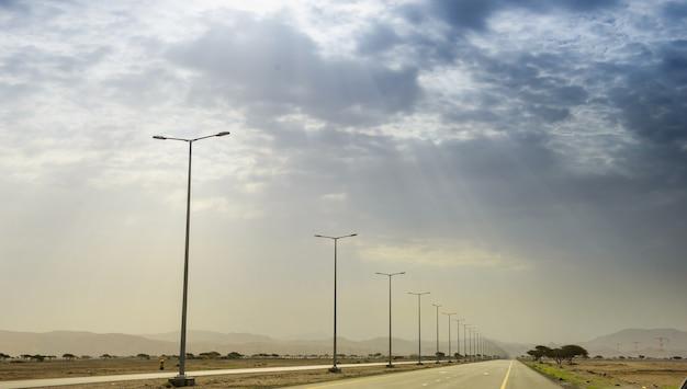 Kręta czarna asfaltowa droga przez wydmy w oazie liwa, zjednoczone emiraty arabskie