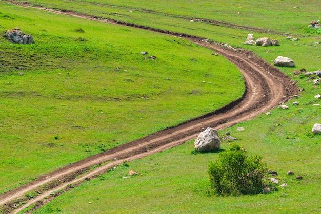 Kręta droga gruntowa wśród zielonego pola