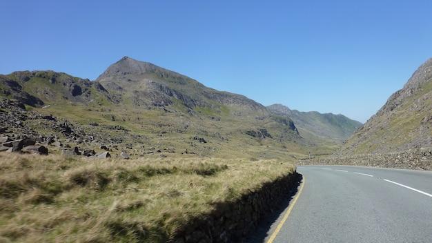 Kręta droga między górami w jasny, słoneczny dzień