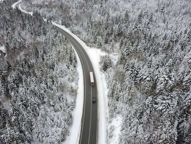 Kręta droga przez lasy zimą. asfalt przez przełęcz na szczyt góry w rumunii