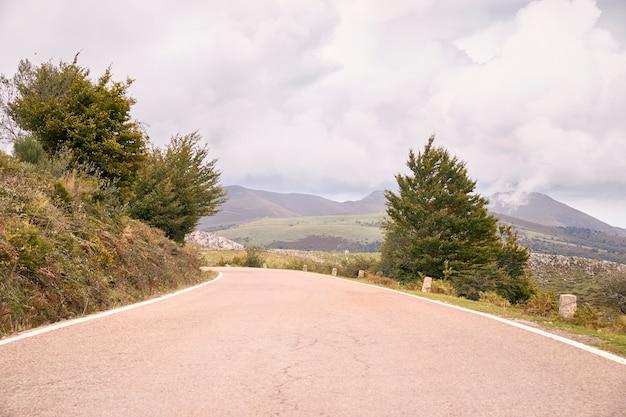 Kręta górska droga między zielonymi polami pod jesienią chmur