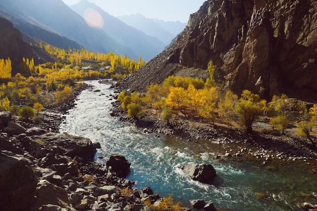 Kręta rzeka płynąca wzdłuż doliny w łańcuchu górskim hindu kush. sezon jesienny w pakistanie