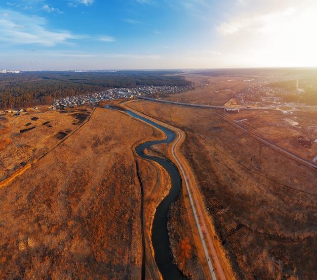 Kręta rzeka w polu z suchą trawą