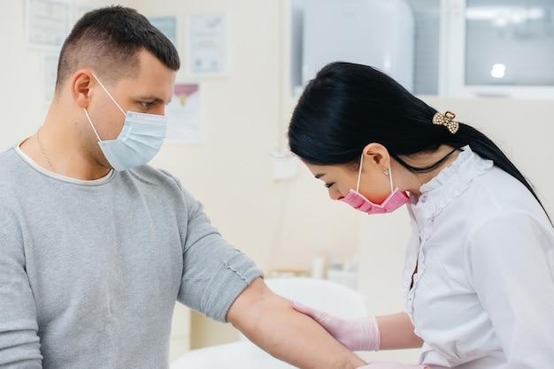 Krew mężczyzny jest pobierana z żyły w celu analizy i testów na obecność wirusów. tworzenie układu odpornościowego i przeciwciał.