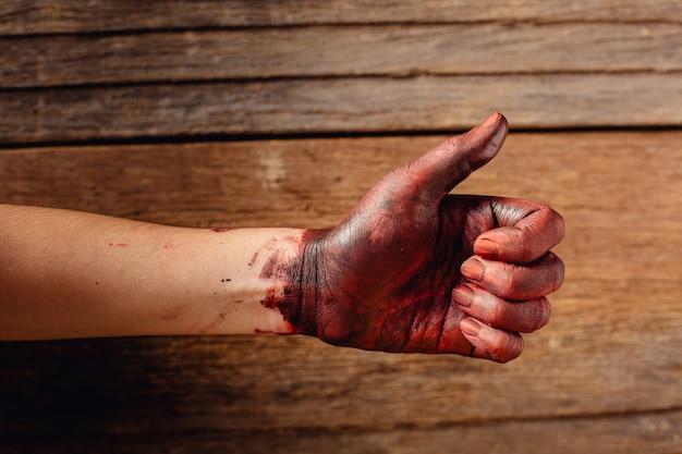 Krew na dłoni z kciukami do góry na drewnianych