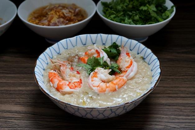 Krewetka zupa z gotowanego ryżu lub owsianka z krewetek w misce ze smażonym czosnkiem i oliwą kolendrową