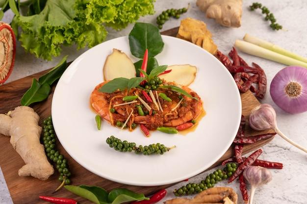 Krewetki chuchi na talerzu ze świeżymi nasionami pieprzu