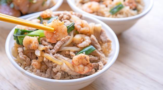 Krewetki duszone na ryżu w misce z pałeczkami