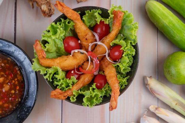 Krewetki głęboko smażone w cieście umieszczone na sałatce i pomidorach w drewnianej misce.