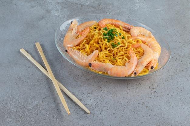 Krewetki i makaron na szklanym naczyniu obok pałeczek na marmurowym tle.