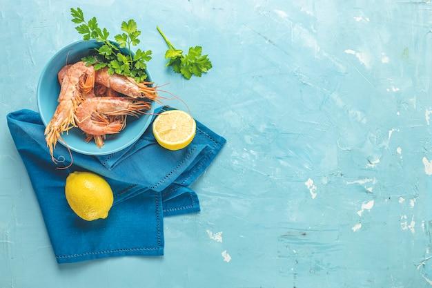 Krewetki, krewetki z natką pietruszki w niebieskim talerzu ceramicznym otoczone serwetką i cytryną na jasnej, klasycznej niebieskiej powierzchni stołu betonowego