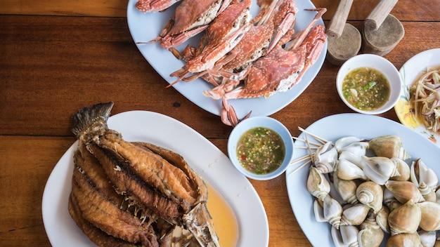 Krewetki na parze, gotowany ślimak morski i głęboki smażony bas morski z pikantnym sosem z owoców morza