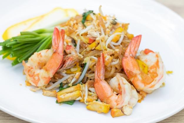 Krewetki pad thai (dania kuchni tajlandzkiej) na białym talerzu