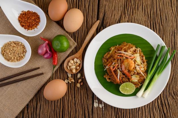 Krewetki padthai w czarnej misce z jajkami, szczypiorkiem i przyprawami na drewnianym stole.