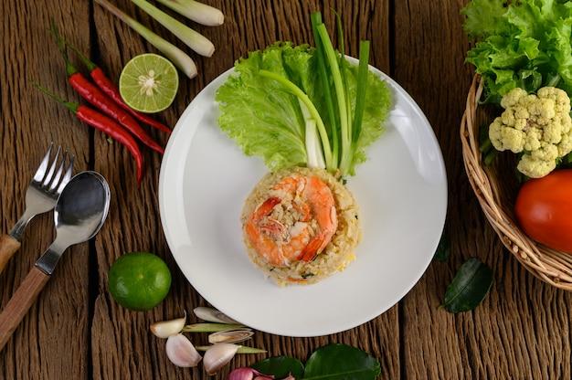 Krewetki smażony ryż na białym talerzu na drewnianym stole