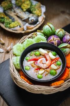 Krewetki - sos pasty z warzywami, omlet, smażone makrele na drewnianym stole.