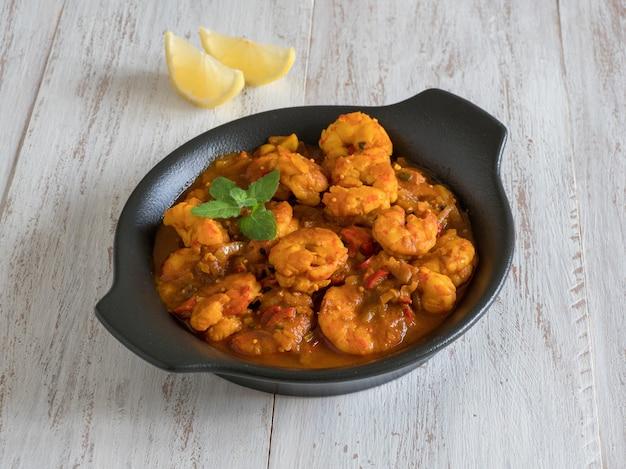 Krewetki w sosie curry z bliska czarnej patelni