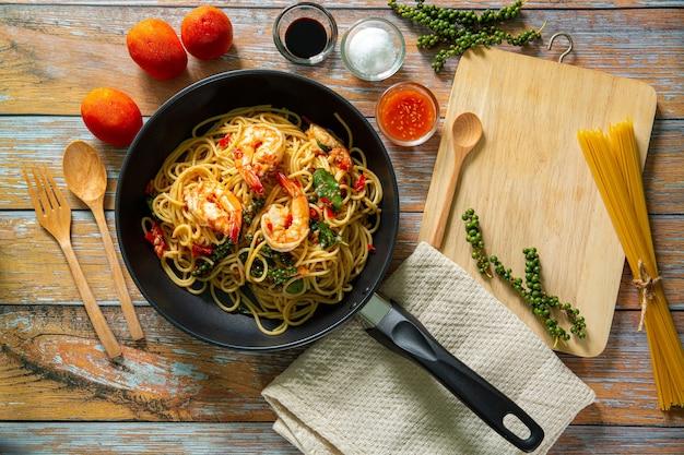 Krewetkowe spaghettiwymieszaj smażony makaron z warzywami i krewetkami w czarnej żelaznej patelni łupkowe tło