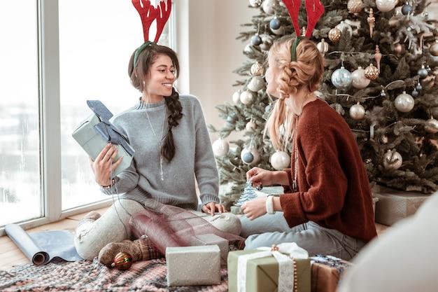 Krewni i przyjaciele. atrakcyjne wesołe panie ubrane w oversize'owe swetry i jelenie uszy podczas dekorowania prezentów świątecznych