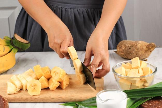 Krojenie banana, przygotowanie kompot bananowy ze słodkich ziemniaków (kolak pisang ubi). dojrzały banan, słodkie ziemniaki, cukier palmowy (gula merah), liście pandan, mleko kokosowe. popularny na śniadanie wramadanie